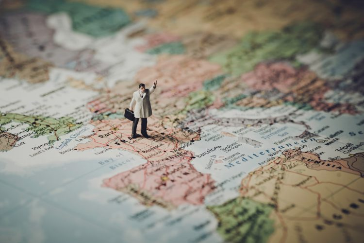 Photo of a map showing Europe with France in the foreground and a plastic male figurine wearing a beige trench coat and holding a black briefcase
